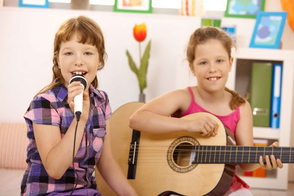 two little girls in childcare playing musical instruments